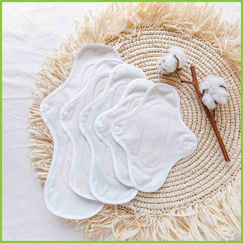 Large, medium, small and panty liner sized cotton pads fanned out on a natural coloured mat.