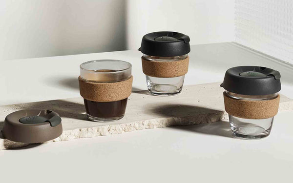 A white table with three glass reusable coffee cups from KeepCup sitting on it. One cup has coffee in it with the lid off, two cups are empty but with the lids on.