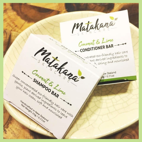 Two small white boxes from Matakana Skincare, one travel shampoo bar and one travel conditioner bar.