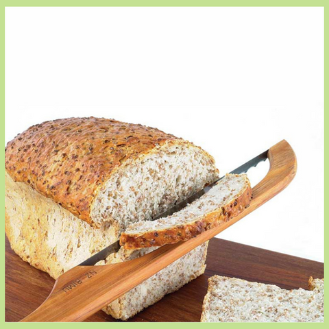 A loaf of bread being sliced with a New Zealand made bread knife.