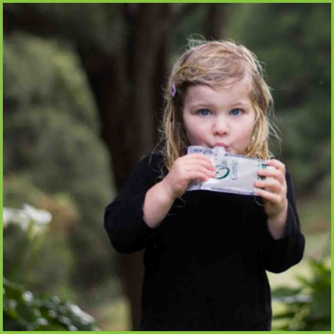 A girl, about 4 years old, eating yogurt from a reusable food pouch whilst outside.