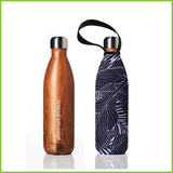 A reusable water bottle made from stainless steel with a wood effect finish. Next to it stands it's protective carry cover with a black and white leaf inspired print.