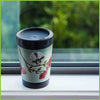 A reusable cup by CuppaCoffeeCup with the Pohutukawa Fantail design sitting on a windowsill.
