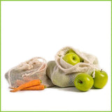 Two reusable veggie bags made from organic cotton. One holding a load of carrots, the other holding a load of green apples.