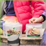 Four zip lock snack bags filled with various snacks such as apple slices, nuts and dried fruit, sitting on a kids playground.