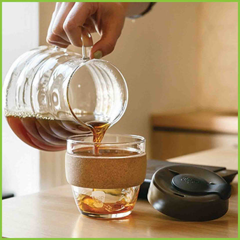 A glass reusable coffee cup from KeepCup having tea poured into it from a glass jug.