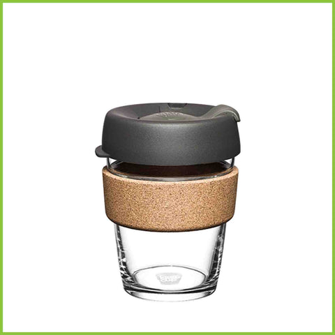 A glass reusable coffee cup from Keep Cup with a dark grey lid and a natural cork band.