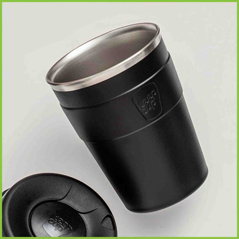 A close up photo of a black stainless steel reusable coffee cup from Keep cup with it's lid off.