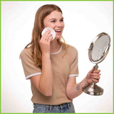 A young woman cleaning her face with reusable make up pads whilst looking into a shaving mirror.