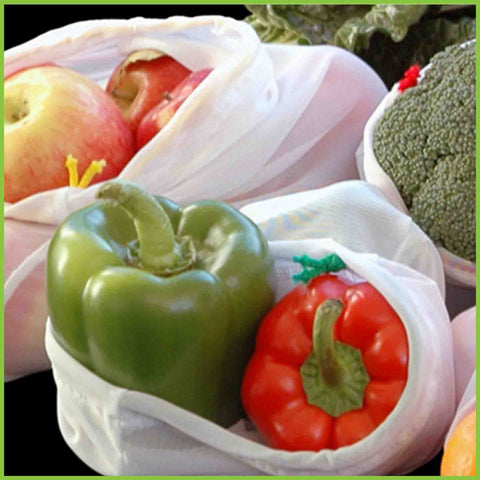 A close up photo of capsicum, broccoli and apples in reusable veggie bags.