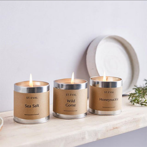 Three St Eval scented candle tins on a shelf