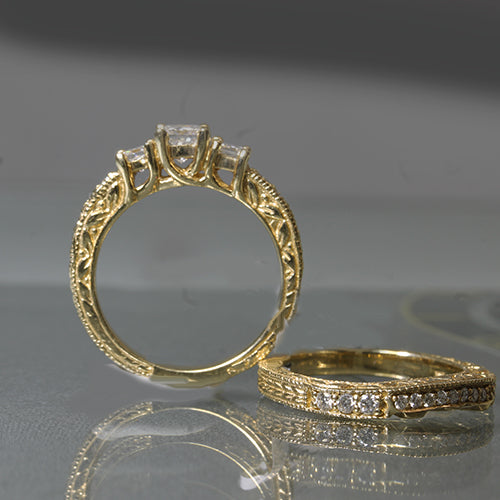 Previously owned 14k yellow gold 3 stone princess cut diamond engagement ring set.