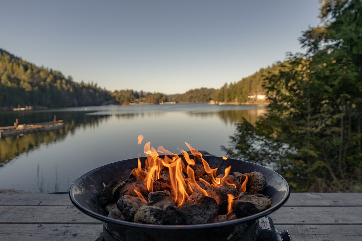 A burning fire in a fire pit on a wooden decking beside a picturesque lake