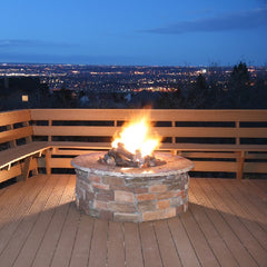 Built in fire pit on decking with fire burning and city lights in view