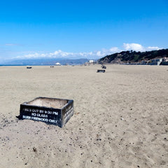 Large square fire pits scattered on the sand along a beach