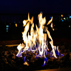 A gas fire pit burning at night with blue and yellow flames