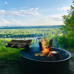 Fire burning in fire pit day time beside a river and greenery