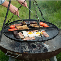 Cooking up a breakfast feast on a hanging grill over an open fire pit