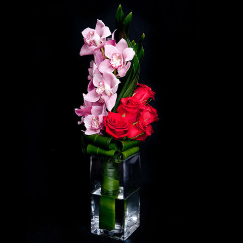 Cymbidium Orchids and Roses in a Simple Glass Container