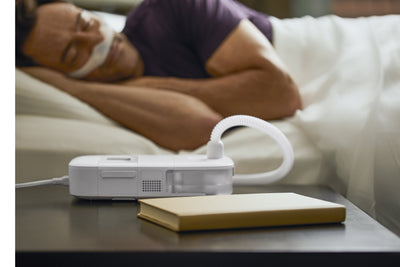 Man sleeping in hotel wearing mask and CPAP Go device on dresser next to bed