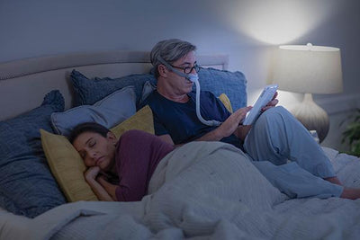 Man reading in bed wearing the AirFit™ N30 mask