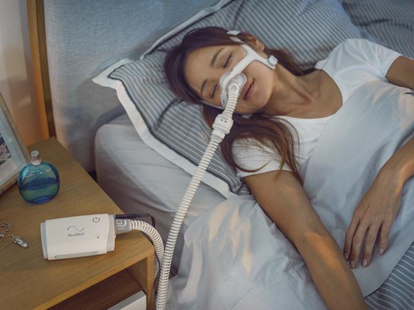 Woman sleeping wearing mask with AirMini™ sitting on nightstand