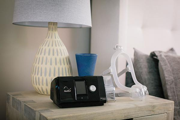 AirSense™ 10 sitting on nightstand with AirFit™ F30i mask attached