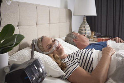 Woman sleeping wearing the N30i mask and AirSense™ 10 sitting on nightstand