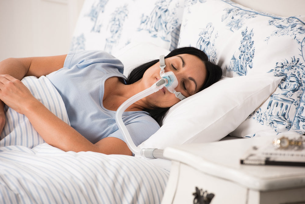 Woman sleeping wearing Brevida nasal pillows mask