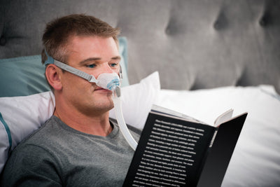 Man reading in bed wearing Brevida nasal pillows mask