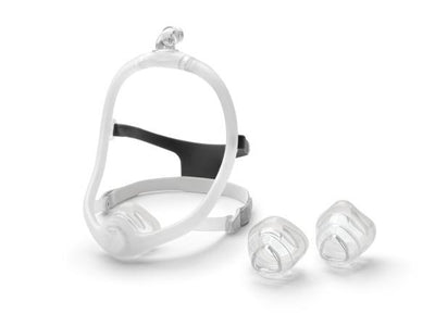 Nasal mask with headgear attached and extra cushions beside