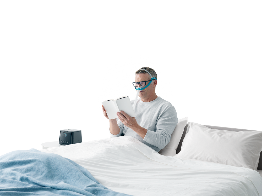 Man reading in bed wearing Evora mask with glasses on