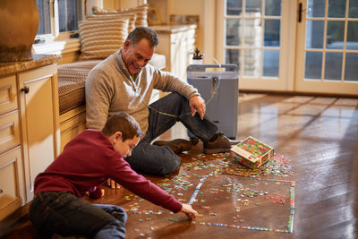 Man using the Everflo while doing a puzzle with his son