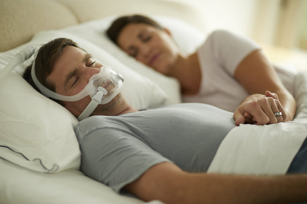Man sleeping on his back wearing full face mask