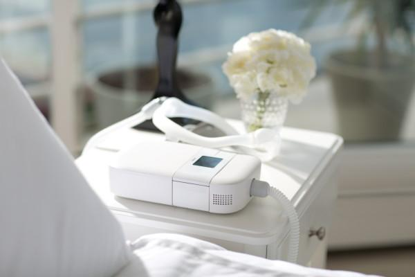 CPAP Go device with battery pack and tubing attached sitting on a nightstand in a cruise ship room