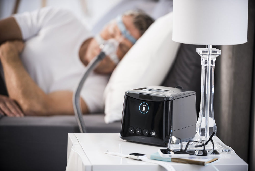 SleepStyle Auto CPAP device sitting on nightstand with Man sleeping wearing sleep mask
