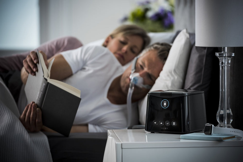 SleepStyle Auto CPAP device sitting on nightstand with Man reading in bed wearing sleep mask