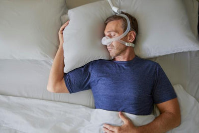Man sleeping on his back wearing nasal mask