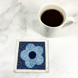 Mug rugs are also known as drink coasters. They are made from 100% cotton fabric, are insulated and washable too. These are great accessories for your home office desk or for your coffee bar area. This particular one is made with blue and white fabrics with a flower appliqued in the center.