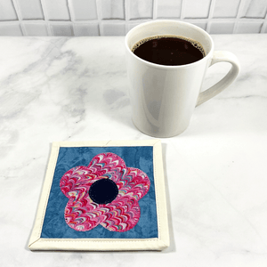Mug rugs are also known as drink coasters. They are made from 100% cotton fabric, are insulated and washable too. These are great accessories for your home office desk or for your coffee bar area. This particular one is made pink and blue fabrics with a flower appliqued in the center.