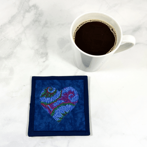 Mug rugs are also known as drink coasters. They are made from 100% cotton fabric, are insulated and washable too. These are great accessories for your home office desk or for your coffee bar area. This particular one is made with a Kaffe Fassett blue fabric made into a heart applique design in the center.