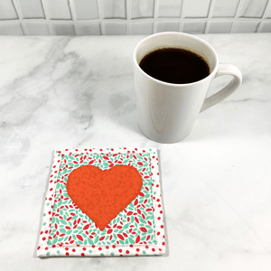 Mug rugs are also known as drink coasters. They are made from 100% cotton fabric, are insulated and washable too. These are great accessories for your home office desk or for your coffee bar area. This particular one is made with a fun coral and aqua speckled fabric background and a solid coral heart appliqued in the center.