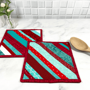 These are a set of two gorgeous red and aqua striped, quilted potholders for your home.  The trivets are made from 100% cotton fabric and are washable.  Practical, yet beautiful when used as hot pads on your kitchen island or dining table.