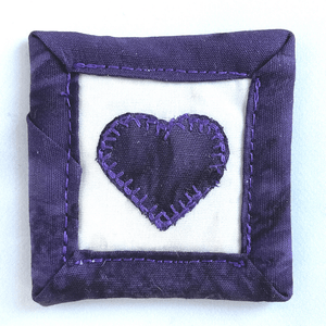 Pocket Hugs are mini quilts that come with a poem card expressing your love.  These are placed in a pocket or purse and are a constant reminder of the love you share.  They measure 2 x 2 inches, are washable, can be ironed and are made from 100% batik cotton fabric.  They come in dark purple, green and aqua, pink, brown, aqua and orange.