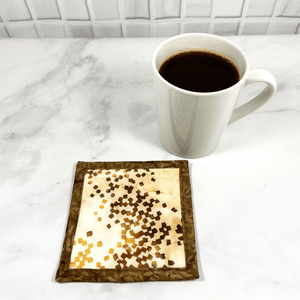 Mug rugs are also known as drink coasters.  They are made from 100% cotton fabric, are insulated and washable too.  These are great accessories for your home office desk or for your coffee bar area.  This particular one is made with a stunning brown and beige batik fabric.