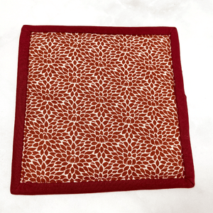 This is a mug rug aka drink coaster that has a gorgeous burgundy and cream Christmas tree applique pattern on the front.  These mug rugs make a great gift for the coffee lover in your life.  It brightens up any table or desk.