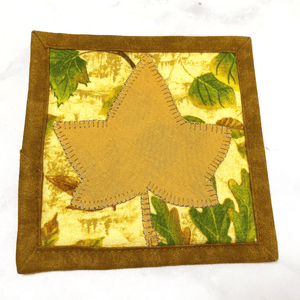 This is a maple leaf themed mug rug aka drink coaster with a gold maple leaf that was appliqued to the front.  These mug rugs make great gifts paired with the recipient's favorite coffee or wine.  The bring a splash of color to any desk or table.