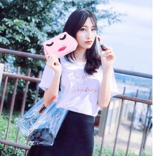 Hong  Kong Influencer holding pink canvas emoji face makeup bag, emma Lomax