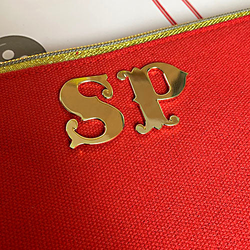 Close up of gold monogram your bag initials on red makeup bag, Emma Lomax