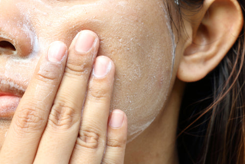 image close up on woman washing face with exfoliant